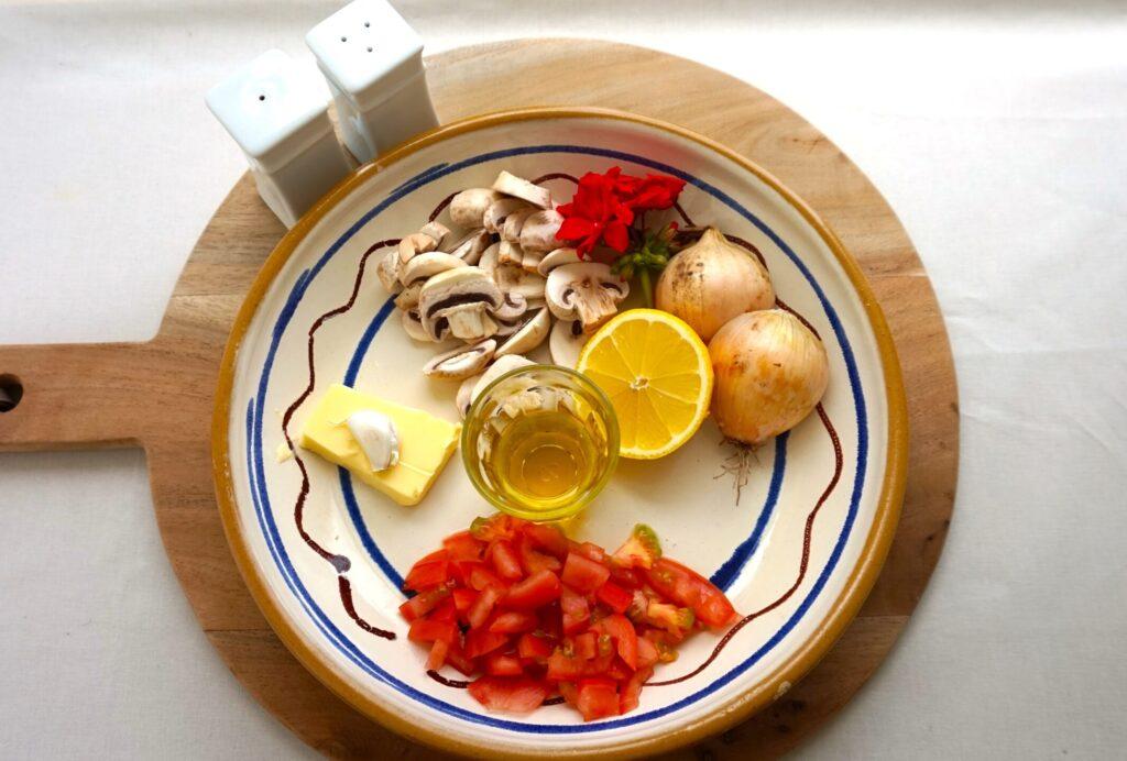 Tallerken med ingredienser: svampe, olie, løg, citron, smør og tomatstykker